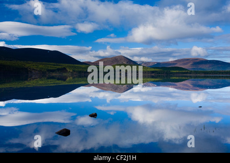 Clouds, forest and mountains reflected upon the still waters of Loch Morlich in the Cairngorms National Park. - Stock Photo