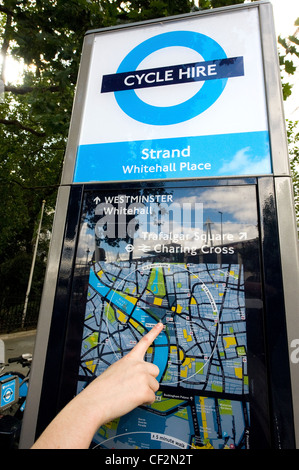 Close-up of a persons hand pointing out their location on a map at a terminal of a Barclays Cycle Hire docking station. - Stock Photo