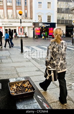 A woman walking past an ashtray full of cigarette butts in a street in Truro. - Stock Photo