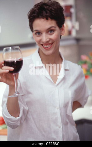 Female short brunette hair wearing white blouse sleeves rolled up, holding large glass of red wine looking to camera - Stock Photo