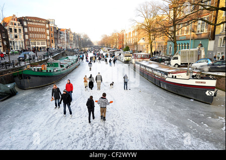 People walk on frozen canals in the center of Amsterdam, Netherlands. - Stock Photo