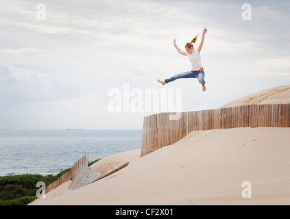 A Woman Jumps Over A Fence In The Punta Paloma Sand Dunes; Tarifa Cadiz Andalusia Spain - Stock Photo