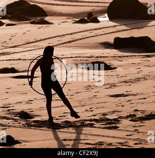 The silhouette of a woman exercising with a hoop on Sennen Beach. - Stock Photo