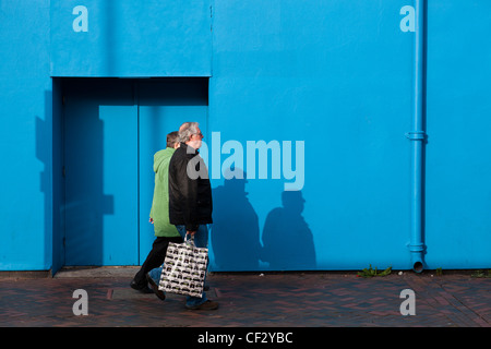 Man and woman walking carrying a shopping basket cast shadows on a blue wall. - Stock Photo