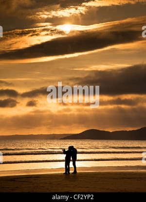 Photographer on Newgale Beach, Pembrokeshire, at sunset. - Stock Photo