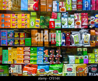 Packets of Chinese food on display in a shop window. - Stock Photo
