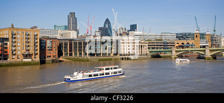 A panoramic view of a sightseeing boat travelling along the River Thames heading towards Southwark Bridge and the City of London