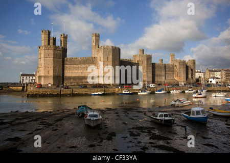 Caernarfon Castle at the mouth of the Seiont river. The castle was begun in 1283 by Edward l as a military stronghold, - Stock Photo