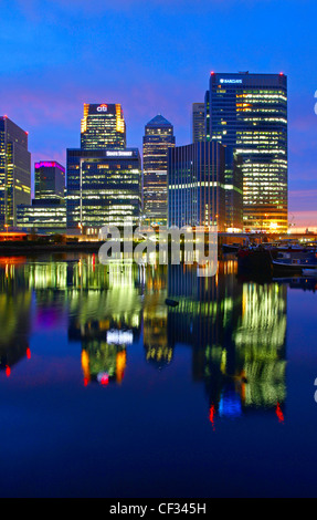 Lights from skyscrapers in Canary Wharf reflected in Blackwall Basin at night. - Stock Photo