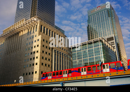 A Docklands Light Railway (DLR) train travelling past the skyscrapers and buildings at Canary Wharf. - Stock Photo