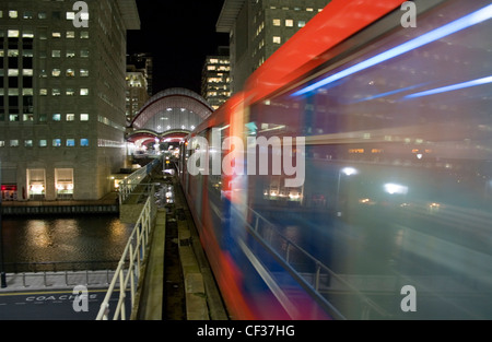 Docklands Light Railway train approaching towards Canary Wharf station at night. - Stock Photo