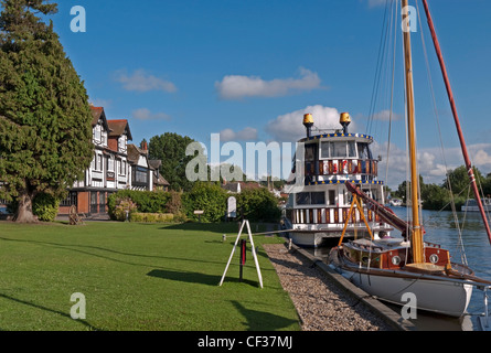 A sailing boat and pleasure boat moored on the River Bure at Horning Staithe. - Stock Photo