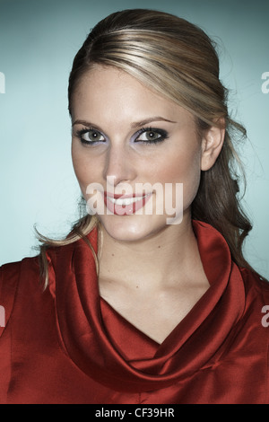 Female wearing red blouse, dark grey and purple eyeshadow and pink glossy lipstick - Stock Photo