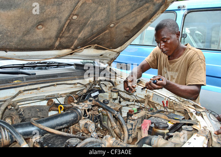A young mechanic works on a car engine in Bo, Sierra Leone - Stock Photo