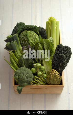A close up of still life of a bowl of green vegetables in a wooden box on white background - Stock Photo