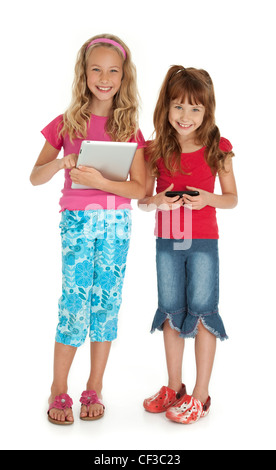 Two young girls standing,holding tablet device and smartphone on white background. - Stock Photo