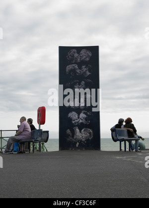 A sculpture of people kissing with two couples sitting either side on the water front in Brighton. - Stock Photo