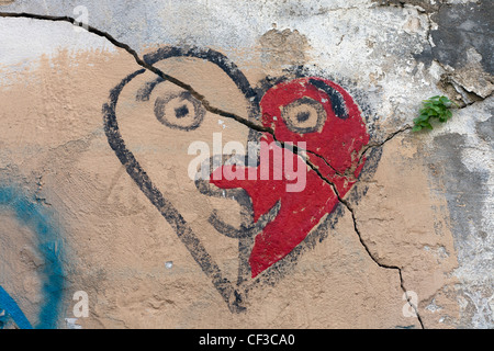 a crack through a painted heart resembling a face on a wall - Stock Photo