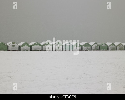 A view to a line of beach huts covered in snow in Hove. - Stock Photo