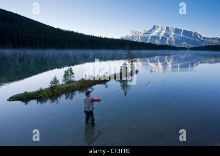 Middle aged male fly fishing in Two Jack Lake, Banff National Park, Alberta, Canada. - Stock Photo
