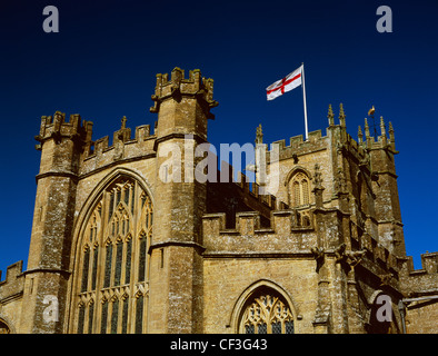 Flag of St George - red cross on a white background - flying from the tower of St Bartholomew's late Medieval church - Stock Photo