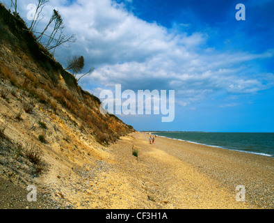 People walking along the beach at Dunwich, once the capital of the Saxon kingdom of East Anglia and a thriving Medieval - Stock Photo