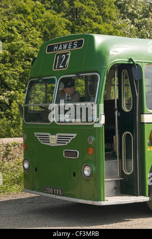 A classic old green bus waiting for passengers outside Leeming Bar station on the Wensleydale Railway, near Bedale. - Stock Photo