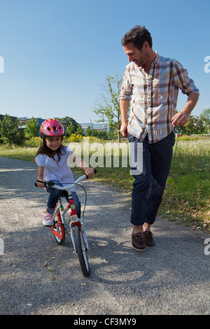 Father running next to daughter on bike - Stock Photo