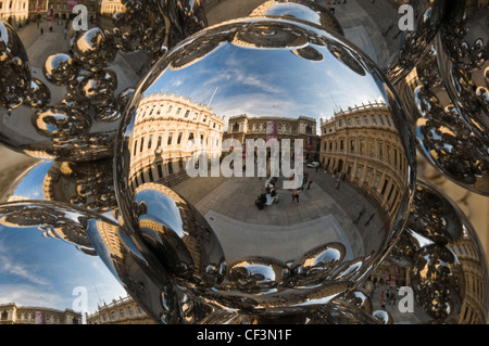 Reflections of the Royal Academy Courtyard in Anish Kapoor's 'Tall Tree and the Eye' sculpture, an arrangement of - Stock Photo