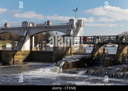 Part of Teddington lock on River Thames near London with weir and bridge. - Stock Photo