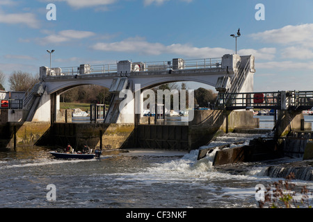 Two fishermen in boat near lock at Teddington on River Thames with weir and cormorant on lock England UK - Stock Photo