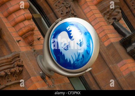 A Barclays bank sign mounted on a wall outside a branch of the bank. - Stock Photo