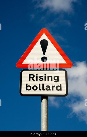 A road warning sign that reads Rising bollard. - Stock Photo