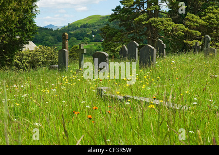 Headstones in the cemetery of St Michael and All Angels' church in Hawkshead. - Stock Photo