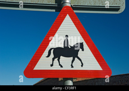 A red triangular warning sign to inform that accompanied horses and ponies use the road. - Stock Photo