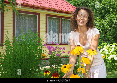 young woman care of flowers in garden near house - Stock Photo