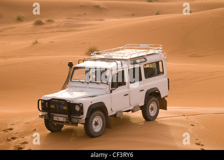 An off road 4x4 vehicle stands in the dunes of the Erg Chebi desert near Merzouga. - Stock Photo