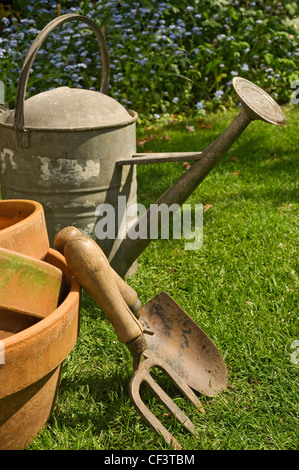 Zinc watering can, trowel, fork and clay plant pots in the garden. - Stock Photo
