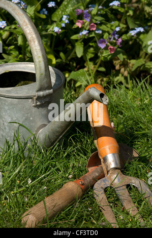 Watering can, hand fork and trowel on a garden lawn. - Stock Photo