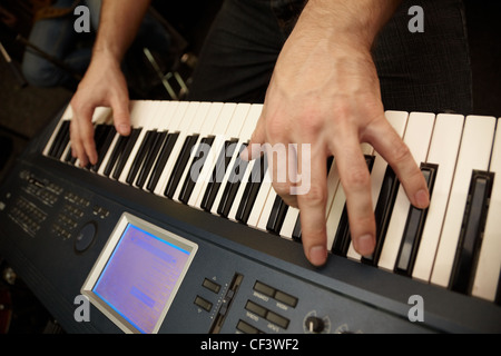 hands of keyboard player on keys of synthesizer. focus on big finger of left hand - Stock Photo