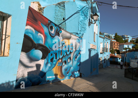 JUZCAR, SPAIN - JUNE 16: Smurfs movie poster on a wall of the village on June 16, 2011 in Malaga, Spain. - Stock Photo