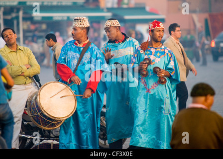 Male dancers in colourful traditional dress perform in the Djema el Fna in Marrakesh at sunset. - Stock Photo