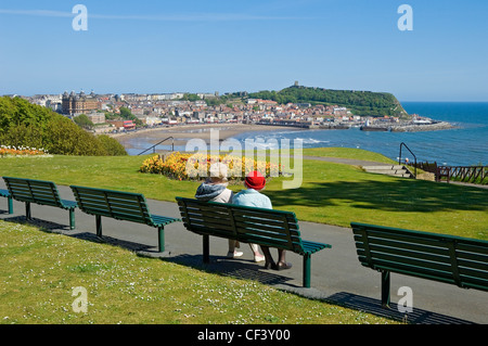 Two elderly women sitting on a bench looking out to sea over South Bay beach. - Stock Photo