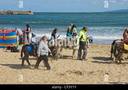 Children enjoying a donkey ride on South Bay beach. - Stock Photo