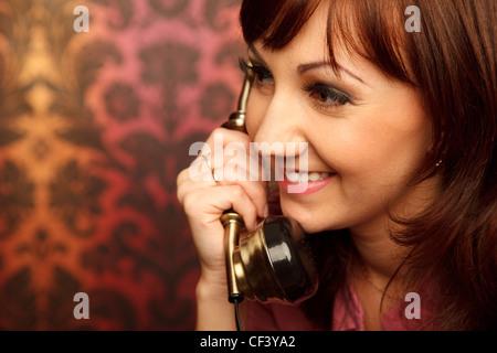 Portrait of girl talking on retro phone. Interior in retro style. Сlose up.