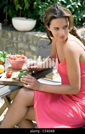 A DayYourself: Female brunette hair tied back loosely wearing short pink sundress orange detail, sitting at wooden - Stock Photo