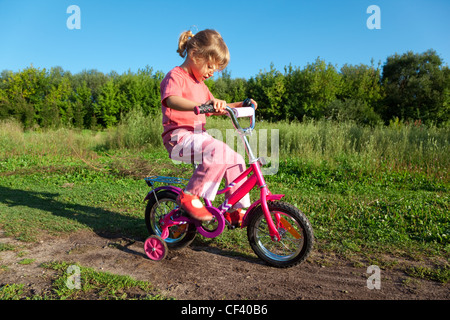 The little girl goes for a drive on a pink bicycle in park - Stock Photo