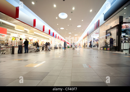 Wide hall and buyers in trading centre with shops on both sides - Stock Photo