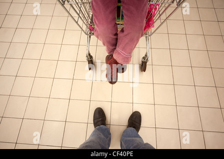 Top view on feet of little girl sitting in shoppingcart and her father standing opposite - Stock Photo