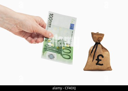 A 100 Euro bill is held in the hand. Near by is a money bag with a Pound currency sign. - Stock Photo